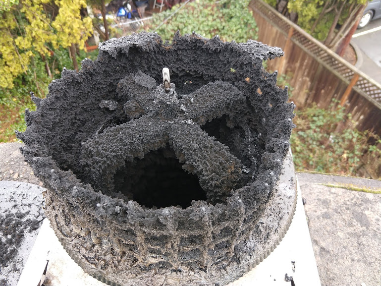 Creosote build-up on a chimney rain cap. The lid of the chimney cap has been removed.