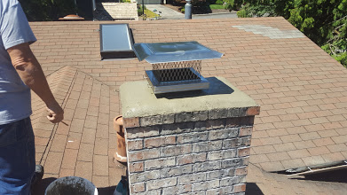 A new stainless steel chimney rain cap installed on top of a chimney.