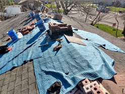 Movers blankets laid out to protect the roof while rebuilding a chimney
